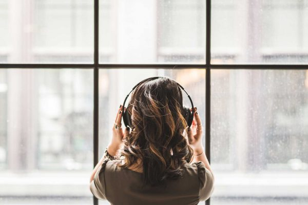 Woman listening to headphones in front of window