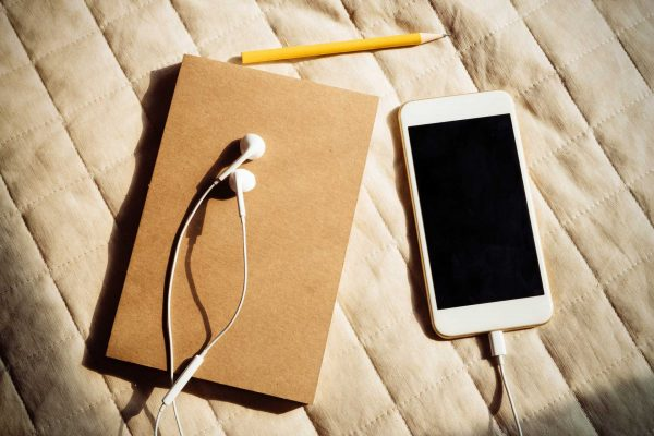 notebook pencil iPhone earbuds on bed